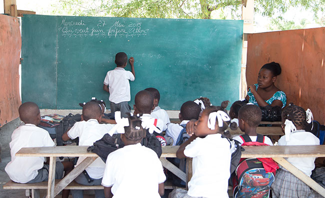 A picture of the children in an outdoor classroom, with a child writing on the chalkboard.